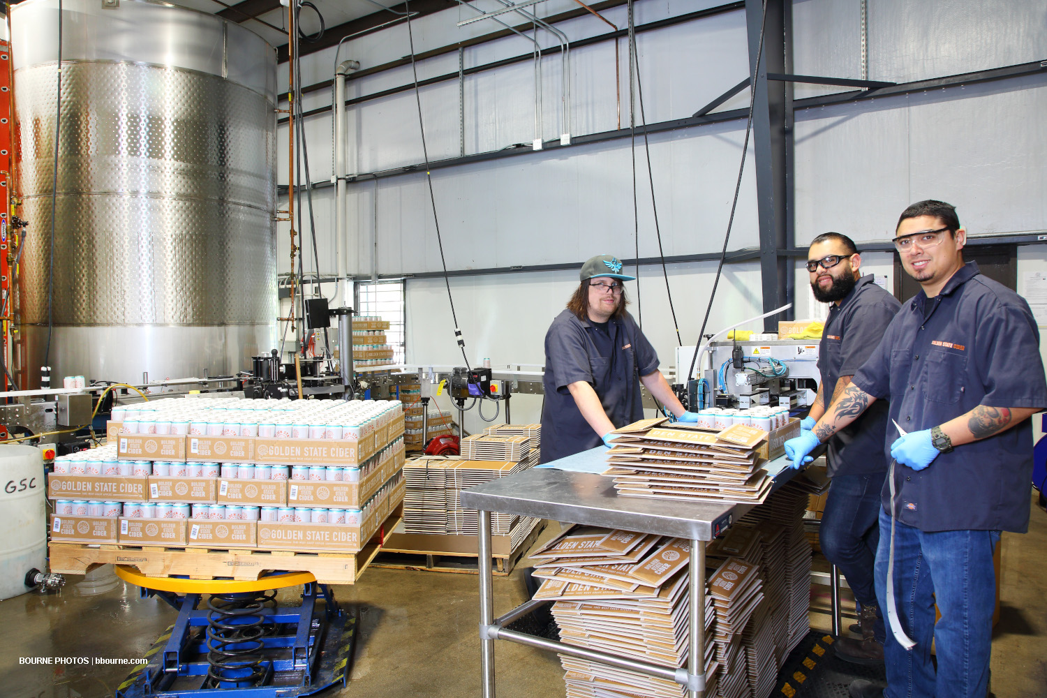 three employees boxing cans of cider in warehouse with cider tank in background.