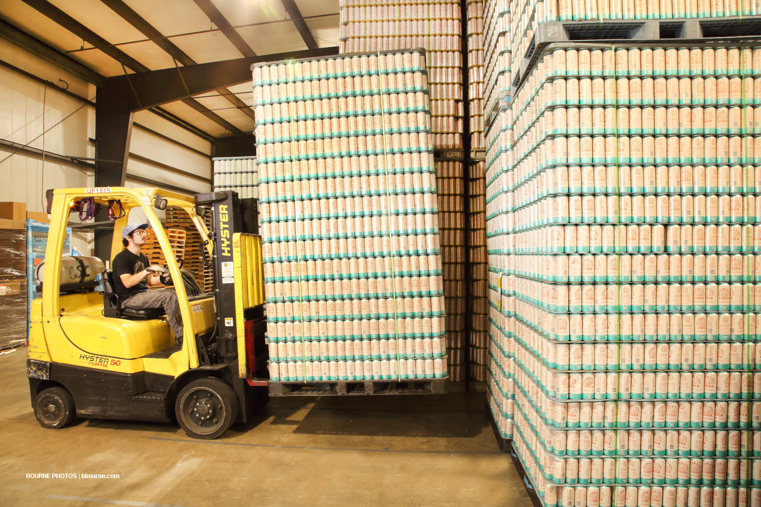 stacked cans of golden state cider on palettes being moved by a forklift in a warehouse.