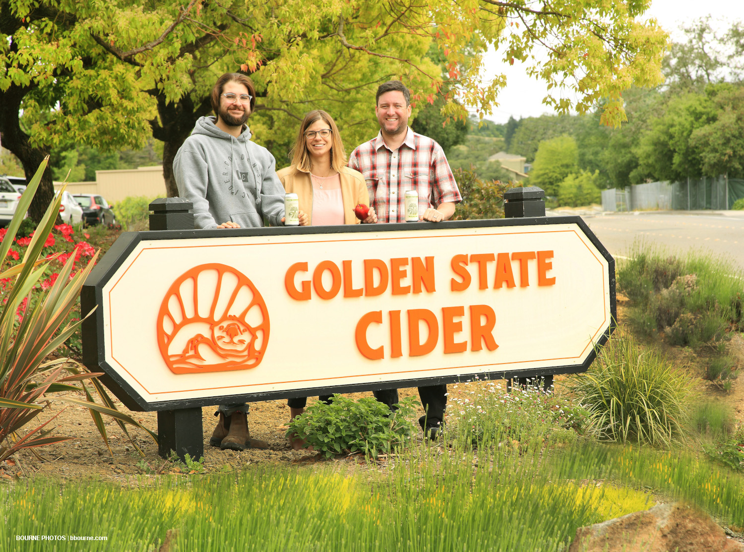 three people standing behind business sign that says golden state cider with a picture of an otter.