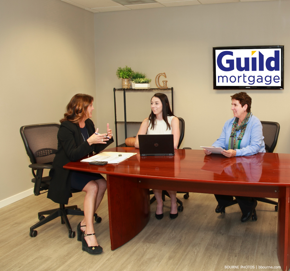 three women sitting at conference table engaged in a meeting.