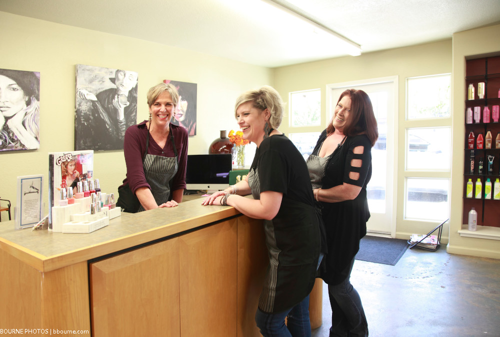 three women laughing and standing inside around reception desk.