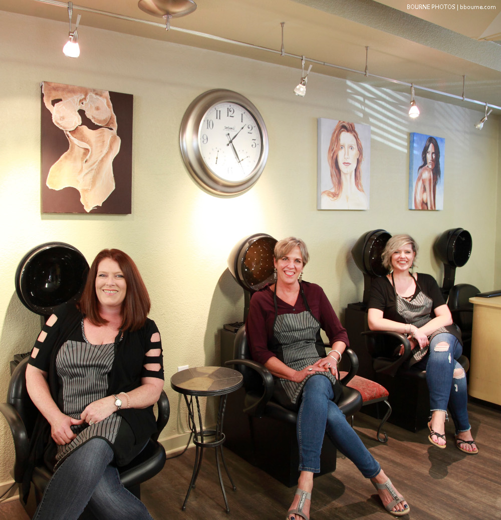 three women sitting at hair drying stations inside hair salon.