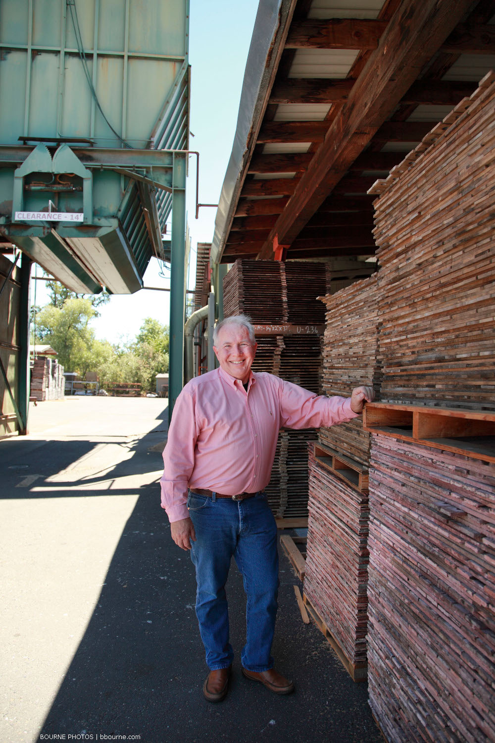 man posing next to stacked lumber at lumber mill