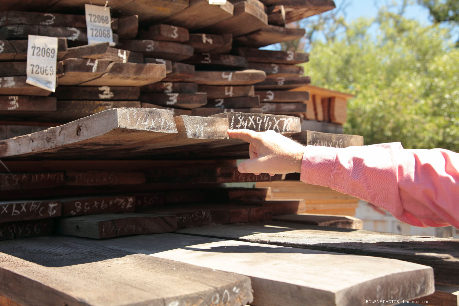 stacked lumber with hand point at stack.