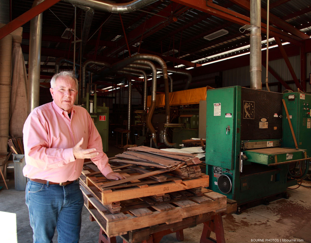 man talking next to wood pallets inside lumber mill.