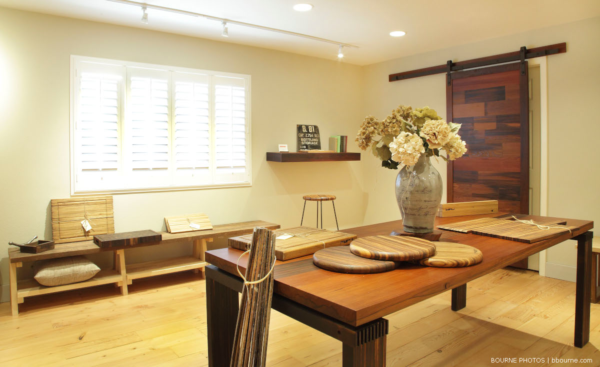 sonoma millworks show room with wooden tables, cutting boards, shelves, stools. Vase of flowers on table.