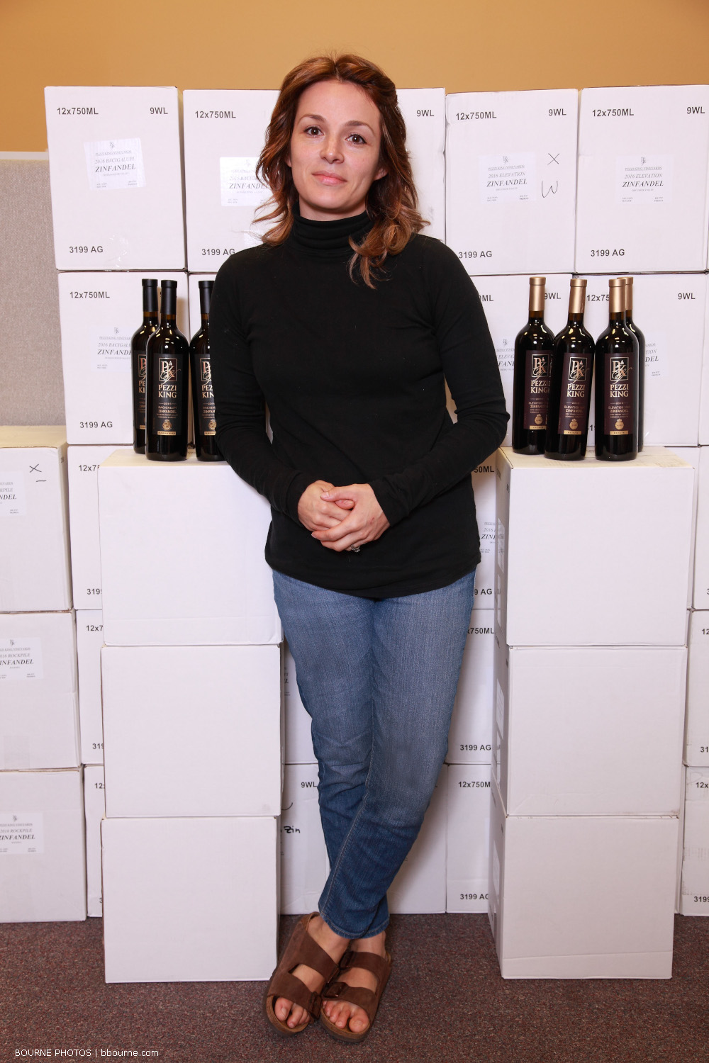 Brittany posing in front of boxes of wine with wine bottles.