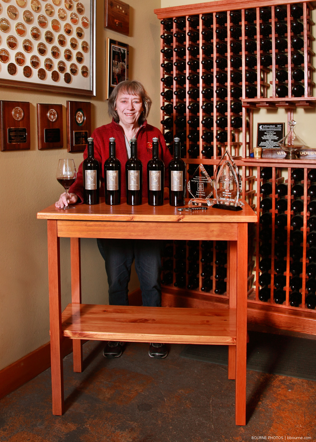 jean posing in tasting room with bottle of wine and a glass of wine in front and medals and more bottle in the back.