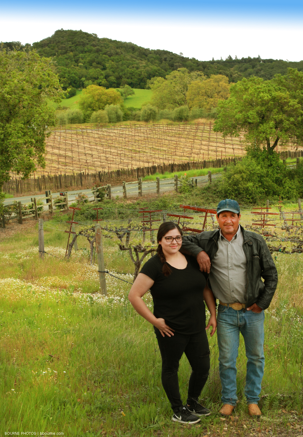 Erica and Juan standing side by side posing in front of rolling vineyards and hills.