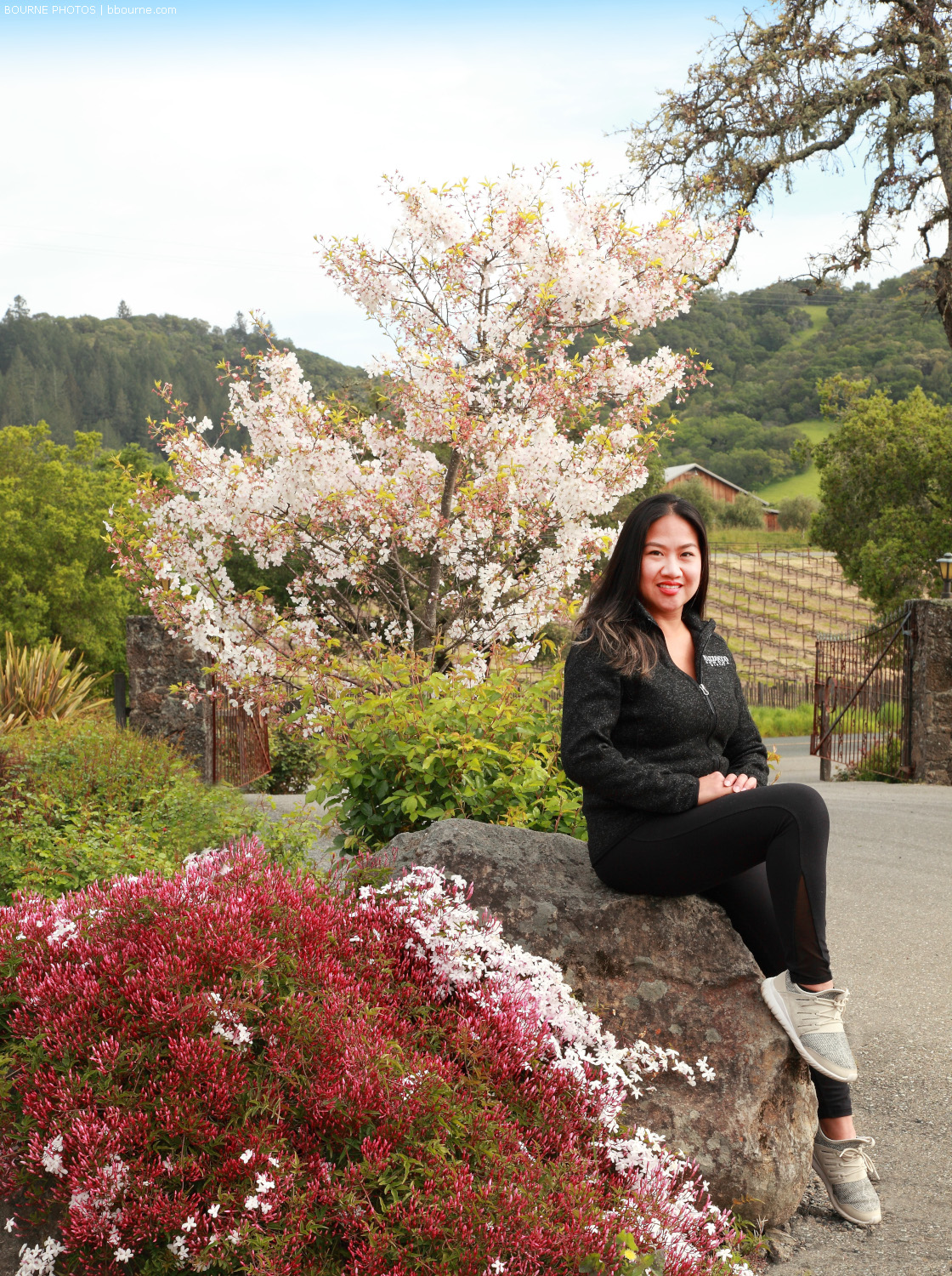 Marjorie posing on a rock surrounded by blooming flowers and plants with vineyard in the background.
