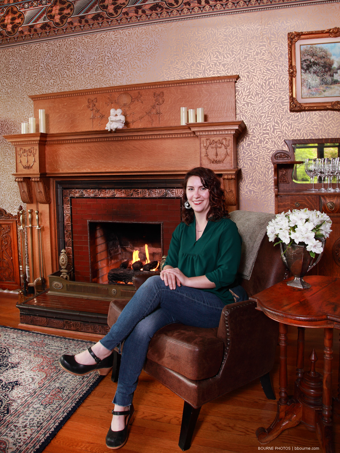 Oceanna posing and sitting in chair in front of fireplace and mantle with small table beside.
