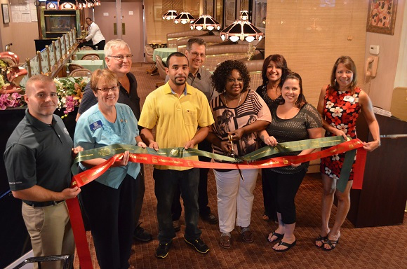 A ribbon cutting to celebrate the Grand Opening of Orchids Carribean Restaurant.