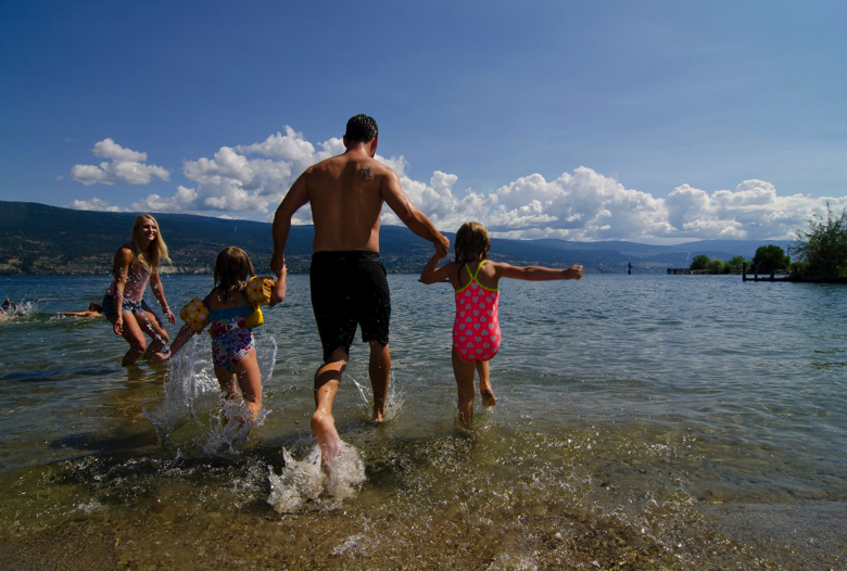 A family enjoys one of the great Summerland BC attractions, our beaches.
