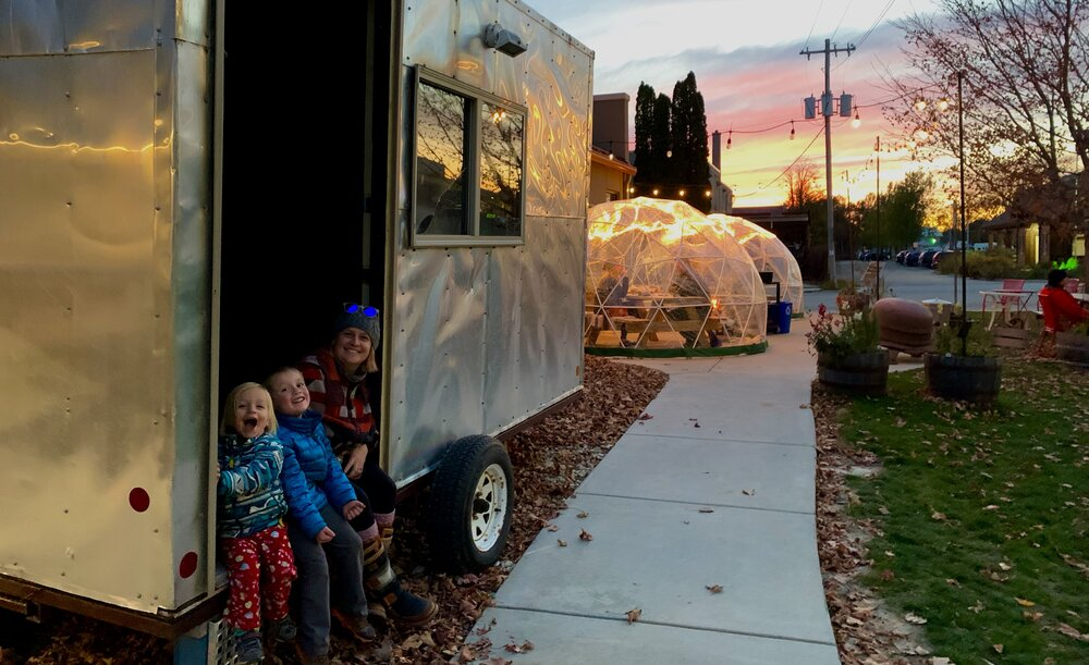 Co-owner, Marie, and her little ones sit enjoying Brix Cider's ice shantys and domes.