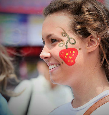woman with strawberry painted on side of face
