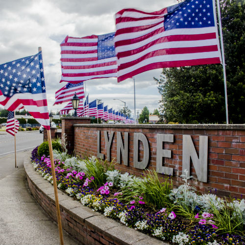 USA flags and Lynden welcome wall with flowers