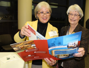 Cathy Wright of the University of West Georgia and Mary Ann Bell of Coweta-Fayette EMC look over the latest edition of the Coweta Healthcare Annual Report during a reception to launch the new report.