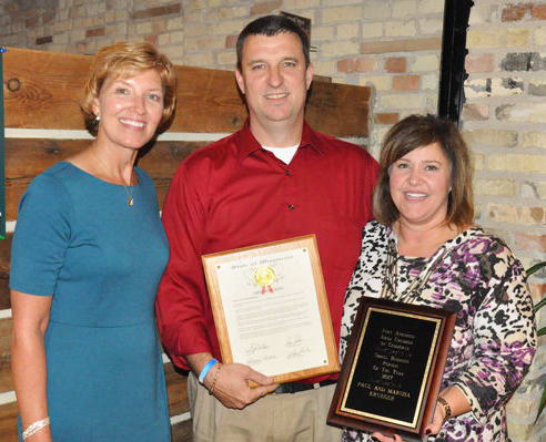 Chamber Executive Director Carrie Chisholm presents Paul and Marsha with their award