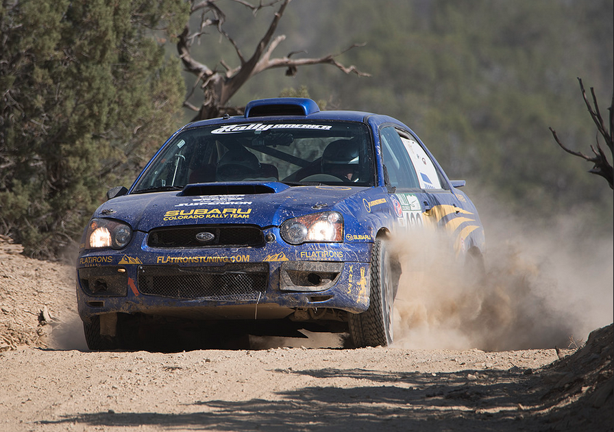 Blue Subaru rally car tops hill.png