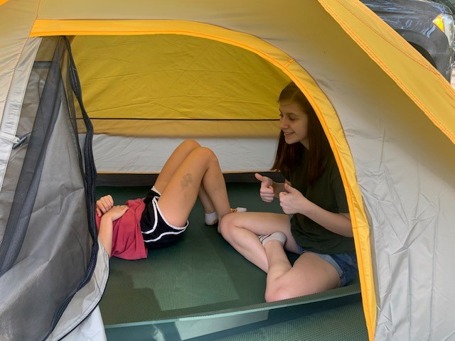 The kids enjoy space in a tent.