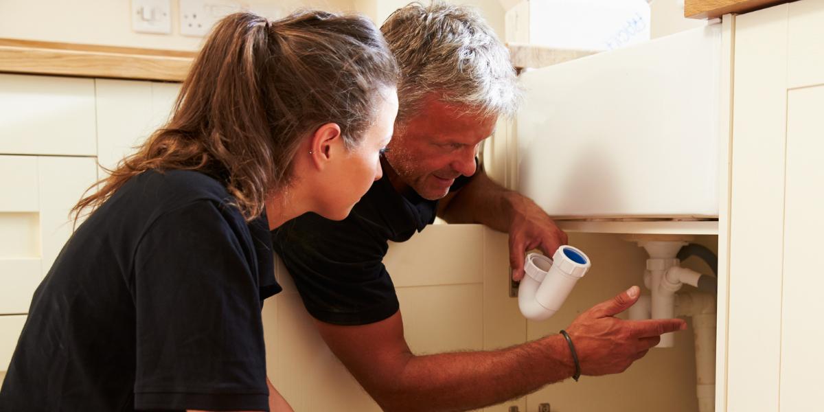 Man teaching women with sink plumbing