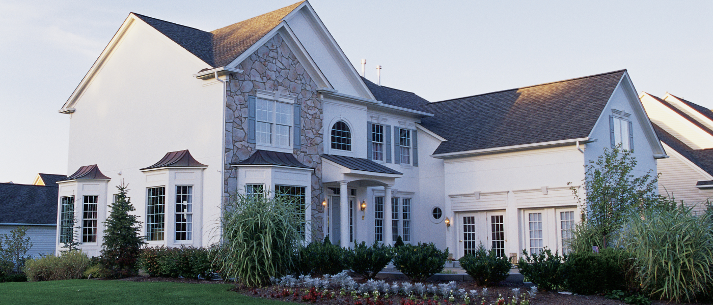 White house with stone feature and landscaping