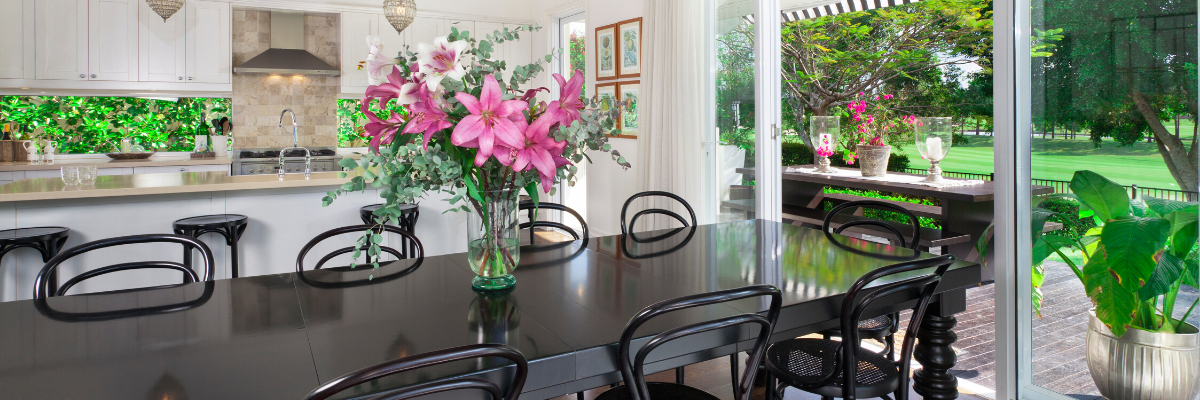 black table and chairs kitchen pink flowers yard with trees and plants