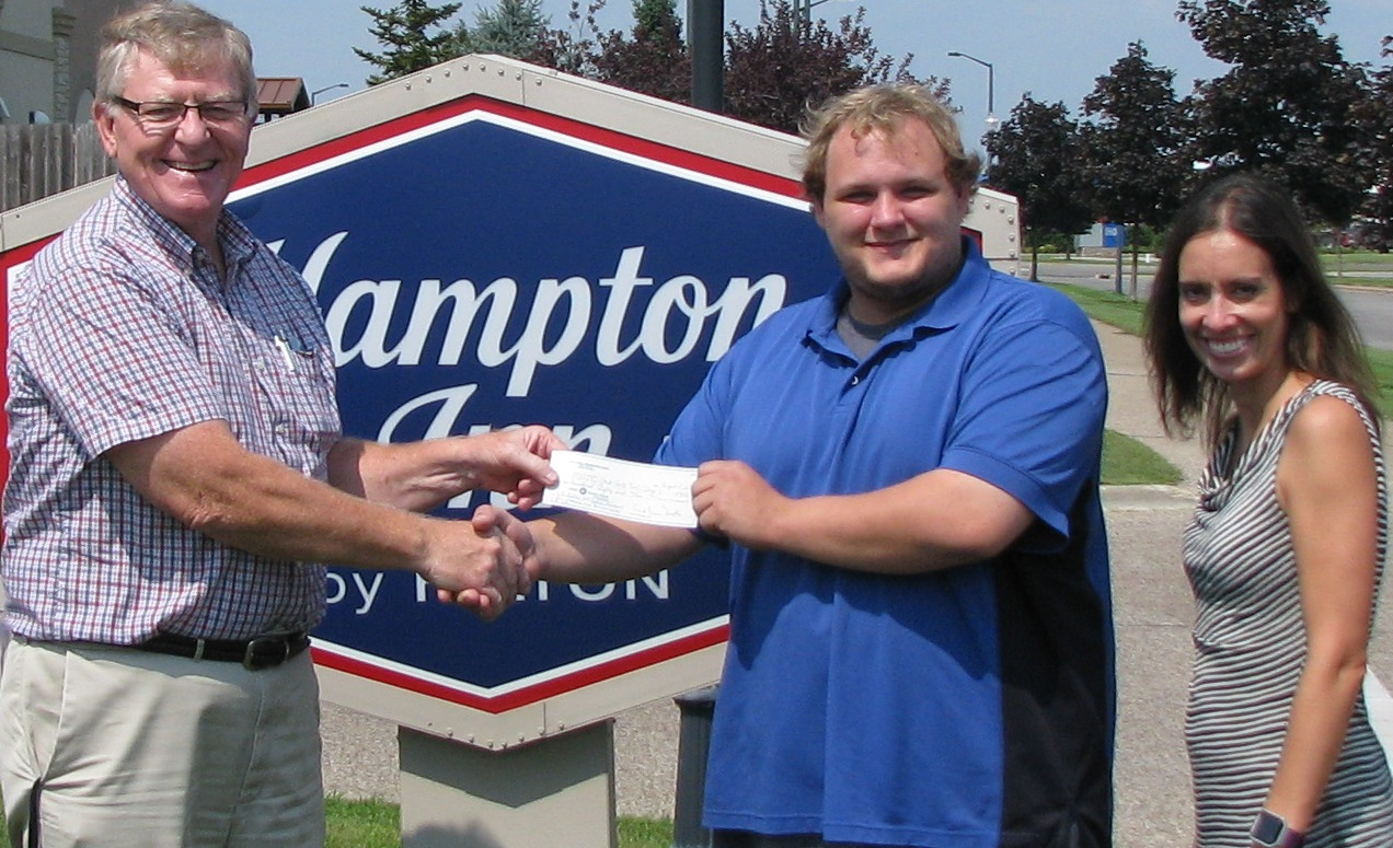 PABA's Ken McKenzie congratulates Tyler Baltus of Hampton Inn on Continuing Education grant as witnessed by Amy Boston, Hampton General Manager.