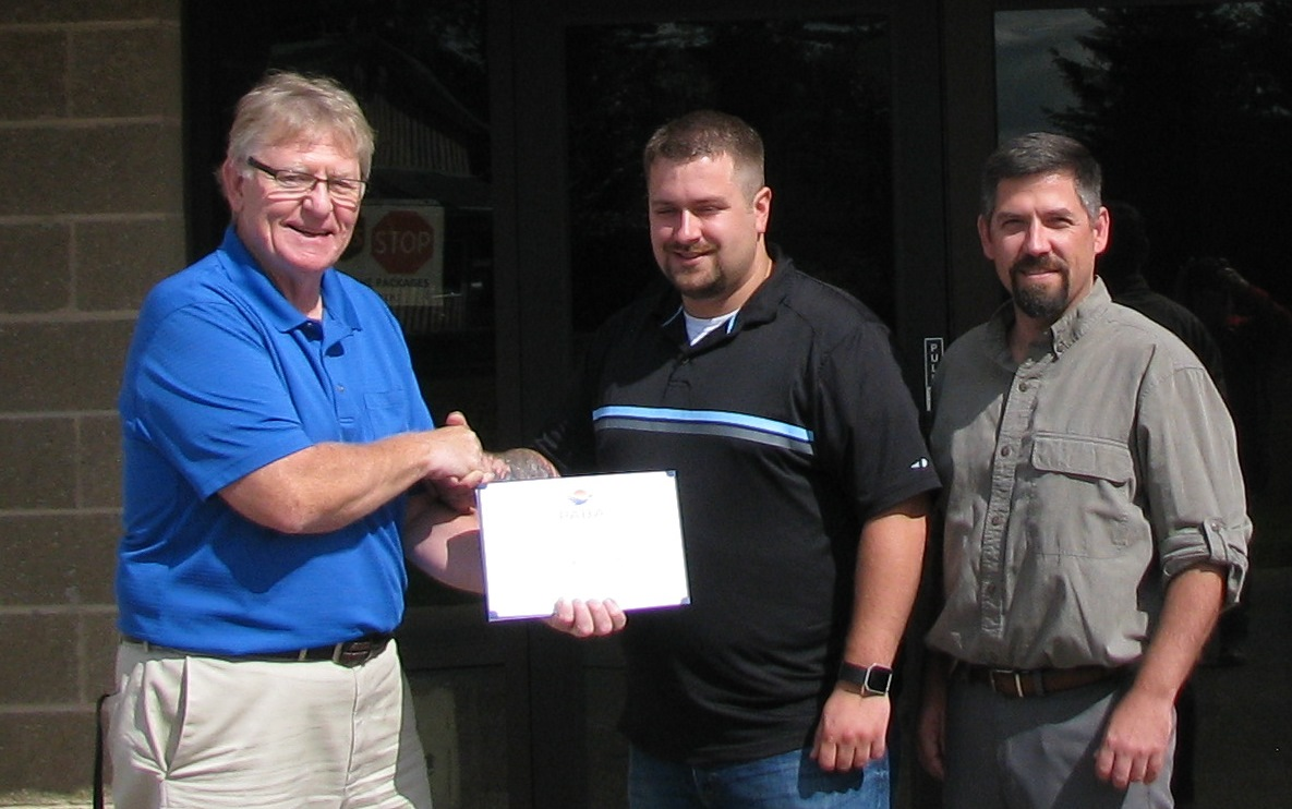 PABA's Ken McKenzie congratulates Jason Nelson of Monogram Appetizers for his Continuing Education grant with Monogram's Nathan Knudson joining in.