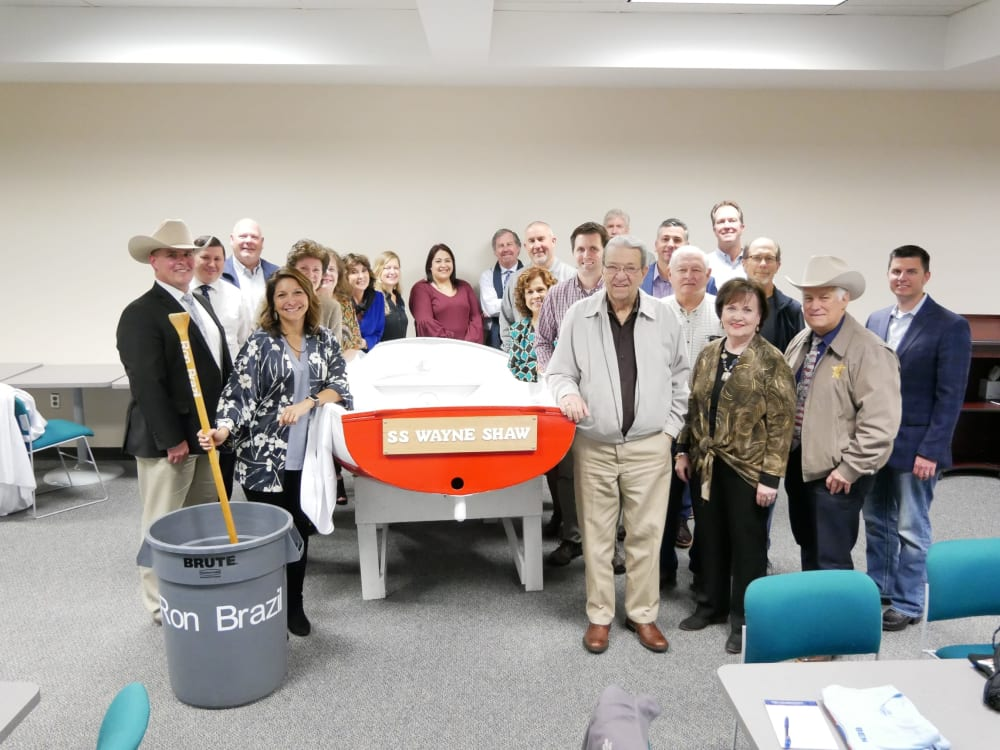 "AT 2019 SESSIONS BRAZORIA COUNTY DAY -At the last planning meeting before the big event.  The Steering Committee unveiled the secret sauce container and paddle, named after Ron Brazil and christened the shrimp boat the ""SS WAYNE SHAW""."