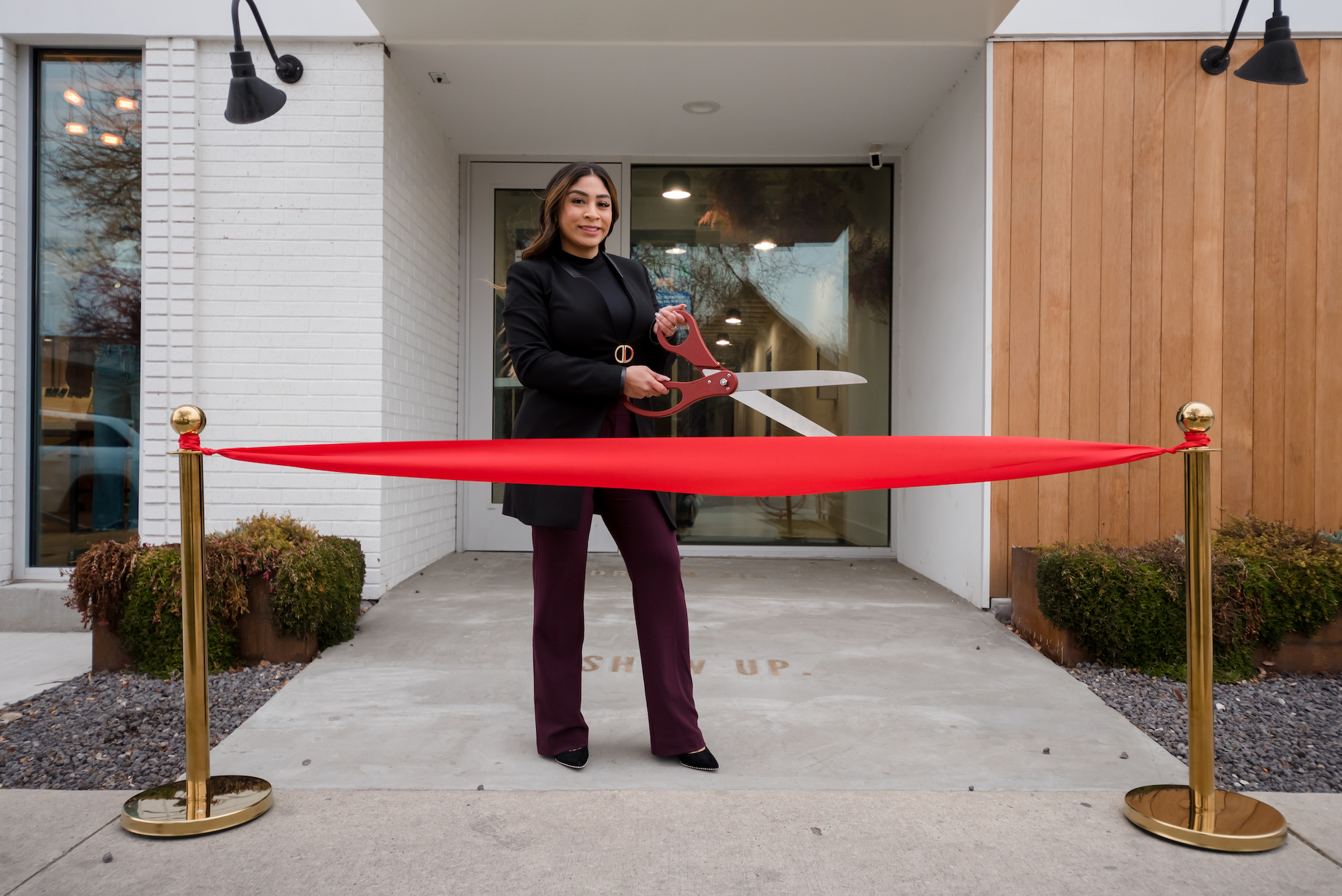 woman smiling at ribbon cutting with giant scissors